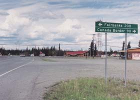 Junction of Tok Cutoff with the Alaska Highway, in ther background; sign in foreground: 208 miles left to Fairbanks, 90 miles right to Canada border