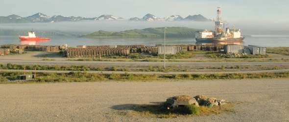 View of Unalaska Bay from Grand Aleutian Hotel, with concrete bunker in foreground, bike path and two-lane paved Airport Beach Road behind it, junk on the shore, and two ships anchored in the bay
