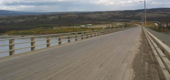 Wooden deck, and grille along the right side covering the pipeline, on the bridge over the Yukon River