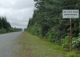 Unpaved Dangerous River Road, with warning sign on lack of winter road maintenance