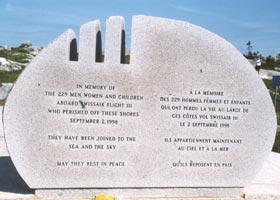 One of two large oval stone markers at Flight 111 memorial, with bilingual remembrance -- In Memory Of | The 229 Men, Women, and Children | Aboard Swissair Flight 111 | Who Perished Off These Shores | September 2, 1998 | They Have Been Joined To The | Sea and The Sky | May They Rest in Peace