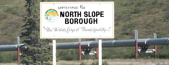 North Slope Borough boundary sign, in front of pipeline