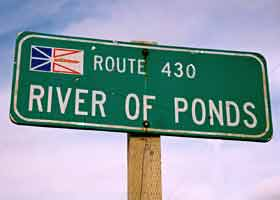 Old-style River of Ponds village sign, including small provincial flag